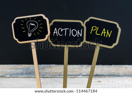 Concept message ACTION PLAN and light bulb as symbol for idea written with chalk on wooden mini blackboard labels, defocused chalkboard and wood table in background #514467184