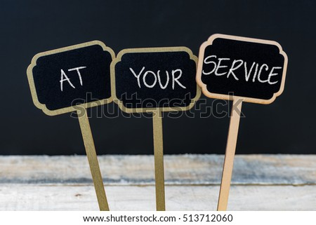 Concept message AT YOUR SERVICE written with chalk on wooden mini blackboard labels, defocused chalkboard and wood table in background #513712060