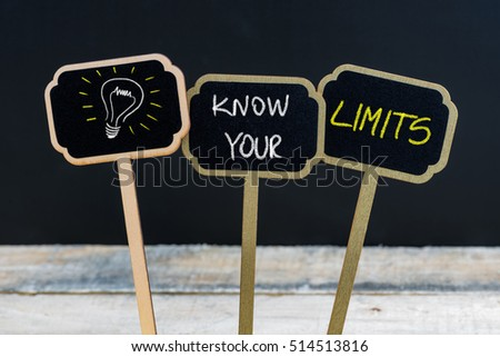 Concept message KNOW YOUR LIMITS and light bulb as symbol for idea written with chalk on wooden mini blackboard labels, defocused chalkboard and wood table in background #514513816