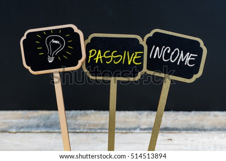 Concept message PASSIVE INCOME and light bulb as symbol for idea written with chalk on wooden mini blackboard labels, defocused chalkboard and wood table in background #514513894