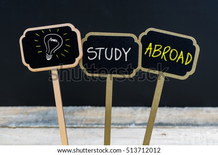 Concept message STUDY ABROAD and light bulb as symbol for idea written with chalk on wooden mini blackboard labels, defocused chalkboard and wood table in background #513712012
