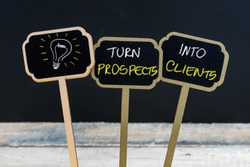 Concept message TURN PROSPECTS INTO CLIENTS and light bulb as symbol for idea written with chalk on wooden mini blackboard labels, defocused chalkboard and wood table in background