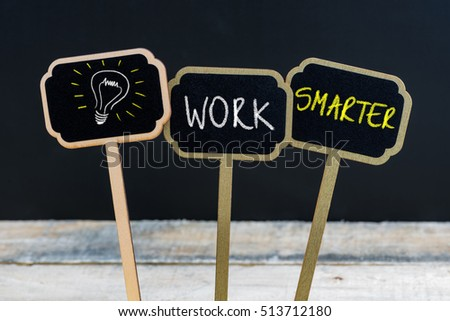 Concept message WORK SMARTER and light bulb as symbol for idea written with chalk on wooden mini blackboard labels, defocused chalkboard and wood table in background #513712180