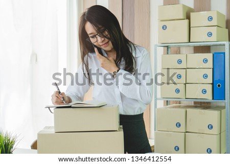 Concept modern new asian entrepreneur. E-commerce business owner calling to supplier to confirm order and reviewing checklist of customer address before sent box of product by parcel post. #1346412554
