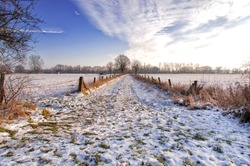 Concept motivation, change or restart: The journey is the goal. Unspoiled winter dirt road in nature with snow, blue sky