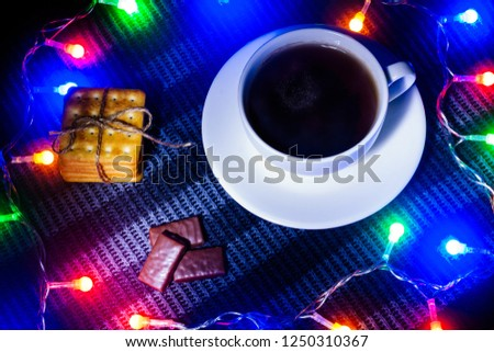 concept new year. Christmas story. a cup of hot tea and cookies and candy in a frame of Christmas garland. dark lighting. view from above. fog for fairytale atmosphere and miracles #1250310367
