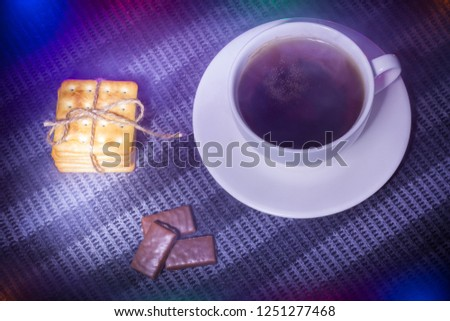 concept new year. Christmas story. a cup of hot tea and cookies and candy in a frame of Christmas garland. dark lighting. view from above. fog for fairytale atmosphere and miracles #1251277468