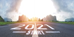 Concept new year, The word start to 2021 Written on The asphalt road in country road Decorate orange light for beauty With a panorama view of grass fields on both sides. The vision new year of 2021