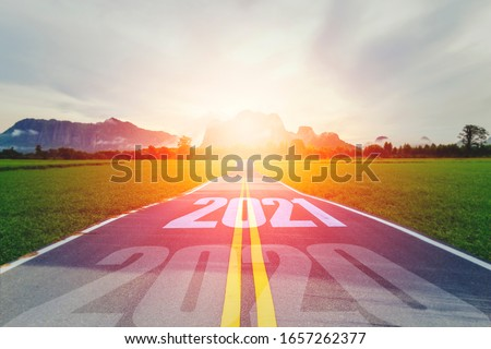 Photo of  Concept new year With The word 2020 to 2021 Written on The asphalt  road in country road Decorate orange light for beauty With With views of rice fields on both sides Concept for new year of 2021