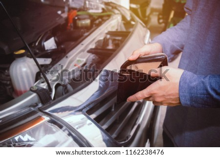 Concept no money : The male car owner holds an empty wallet, no cash for pickup repairs.