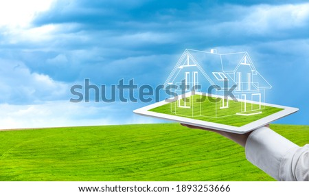 Concept of a dream home. Visualization of the house in the field. Self-sufficient, passive and ecological house. Architect serves the house on the tablet. Foto stock ©