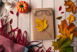 Concept of a fall mood, notebook, red plaid in the cage, candle, leaves, and acorns on a white background.Warm atmosphere,