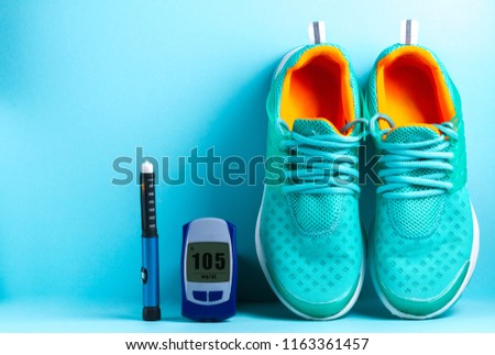 Concept of a healthy lifestyle. Diabetes. Sugar diabetes. Glucose meter, pen for insulin injection and sneakers on a blue background. #1163361457