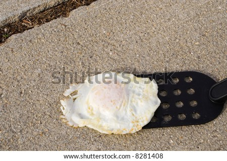 Concept of a hot day. Frying an egg on the sidewalk.