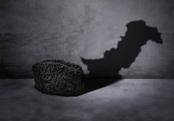 Concept of a karakul cap showing pakistan map in shadow for happy quaid e azam day on gray background.