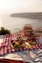 Concept of a summer picnic outdoors with blanket, eco style straw bag with  plate of fruits, cheese and wine. Romantic picnic with seaside and mountain view at sunset