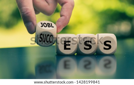 "Concept of a turning point in life. Hand turns a cube and changes the word ""jobless"" to ""success"". #1428199841"