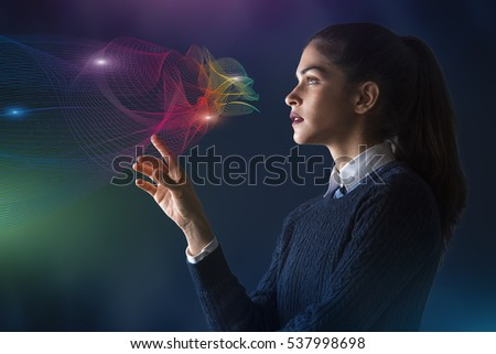 concept of a young woman selecting colors on projected rainbow color spectrum vector lines of cloud shape #537998698