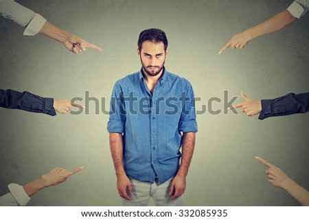Concept of accusation guilty person guy. Sad depressed upset man looking down many fingers pointing at him isolated grey office wall background. Negative human face expression emotion feeling Сток-фото ©