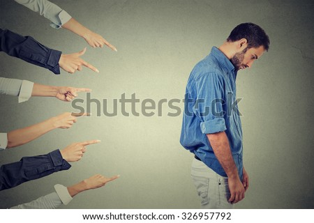 Concept of accusation guilty person guy. Side profile sad upset man looking down many fingers pointing at his back isolated grey office wall background. Negative human face expression emotion feeling Stockfoto ©