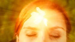 Concept of affirmations for health, wealth, happiness, and fulfilling life. Light beams are coming out of forehead of a young woman showing enlightenment