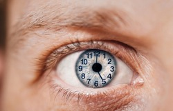 Concept of aging, time flies of man. Clock dial on eye. Close-up