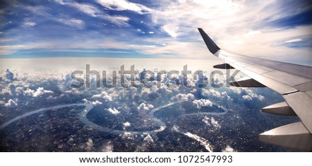 Concept of airplane travel. Flying above the city. Scenery sunset landscape.Sunrise and clouds.Flight and journey to destination #1072547993