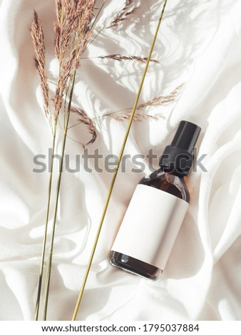 Concept of apothecary cosmetic. Herbs and brown glass bottle of essential oil in still life composition on crumpled white fabric. Sunlight and shadow. Natural cosmetic remedy with white tag.