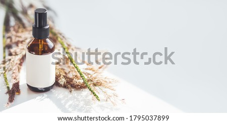 Concept of apothecary cosmetic. Herbs and brown glass bottle of essential oil in still life composition on light blue and white background. Sunlight and shadow. Natural cosmetic remedy with white tag. Stockfoto ©
