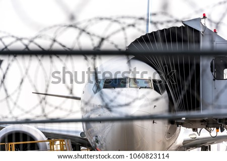 Concept of arresting terrorists on hijacked plane or other aviation incident. Airport security zone. Blurred aircraft behind a barbed wire fence