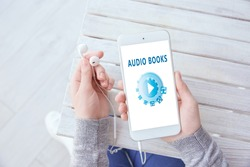 Concept of audio books and modern technology. Woman using smartphone and earphones, closeup