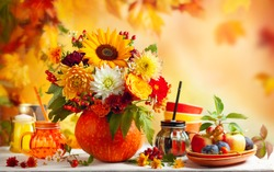 Concept of autumn festive decoration for Thanksgiving day or Halloween. Autumn bouquet of beautiful flowers and berries in a pumpkin, different fruits and drinks on wooden white table.