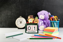 concept of back to school or education with school belongings, open notebook, pencils, scissors, stickers, table clock, cube shape calendar for 1 September and teddy bear on light table