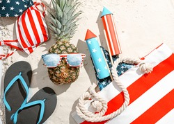 concept of beach party in honor of american independence day 4th july. pineapple with glasses stylized as an American flag on the sand on the beach