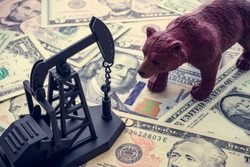 Concept of bear market oil price down falls plummet due to oversupply, deal failure, COVID-19. Oil pump jack and bear on US dollar banknotes. Crude oil commodity trading in price crisis situation.