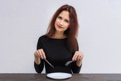 Concept of beautiful brunette girl eating on a white background at the table. She sits in front of the camera with different emotions in different poses.