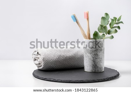 Concept of biodegradable objects. Two bamboo toothbrush in cup near bathroom towel and eucalyptus plant on black plate stand against white copy space background. Oral and dental care Foto d'archivio ©