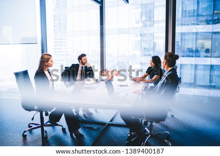 Concept of brainstorming and briefing, positive diverse male and female financial experts discussing information during working time in conference room sitting at desktop with laptop devices #1389400187