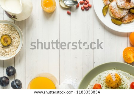 Concept of Breakfast. Fried eggs, cottage cheese pancakes, plums and oatmeal with milk, orange juice on the table.