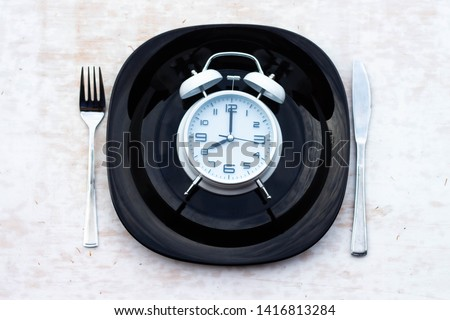 Concept of breakfast time with white alarm clock, black plate, fork, knife. The concept of healthy eating. #1416813284
