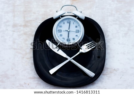 Concept of breakfast time with white alarm clock, black plate, fork, knife. The concept of healthy eating. Do not eat after six in the evening. #1416813311