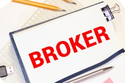 concept of brokerage office, inscription broker on the house, piggy bank on a red background, real estate market.