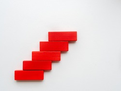 Concept of building success foundation. Women hand put red wooden block in the shape of a staircase