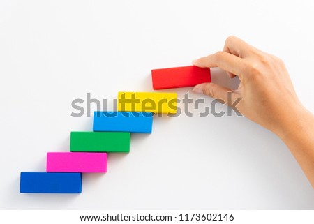 Concept of building success foundation. Women hand put red wooden block on colorful wooden blocks in the shape of a staircase. #1173602146