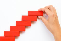 Concept of building success foundation. Women hand put red wooden block on yellow wooden blocks in the shape of a staircase
