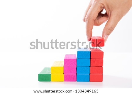 Concept of building success foundation. Women hand put wooden blocks in the shape of a staircase. #1304349163