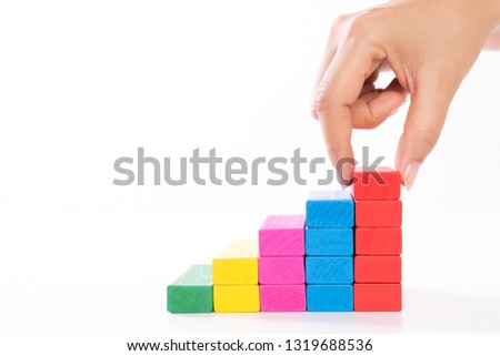 Concept of building success foundation. Women hand put wooden blocks in the shape of a staircase. #1319688536