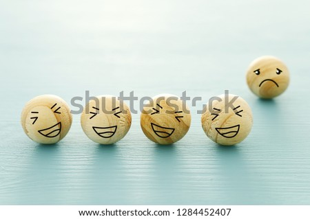 concept of bullying , discrimination. group of laughing emoticon faces and one alone look sad and depressed