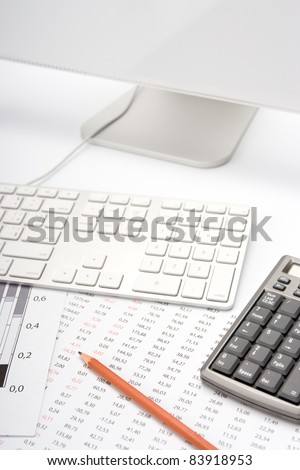 Concept of business analyst workplace - pencil, sheet with numbers, graph, keyboard, computer and calculator