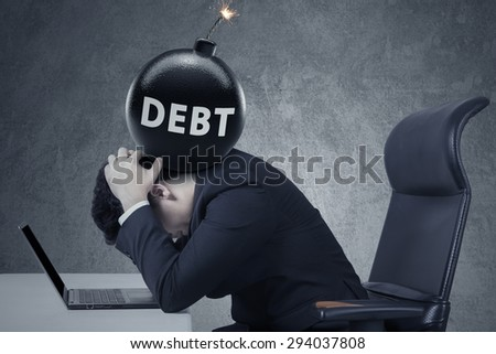Concept of business debt deadline. Stressful businessman with laptop and a bomb of debt on his head
